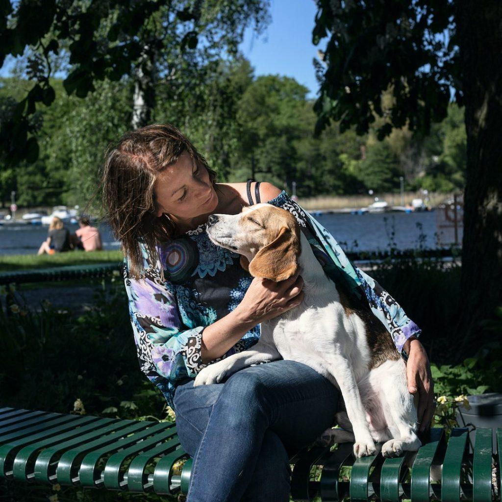 Hundpsykologen Kicki Fellstenius  och beaglen Tage njuter i solen på en parkbänk
